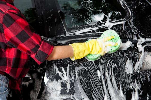 たっぷりの泡で車を洗う女性